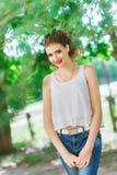Młoda kobieta outdoors w białej koszulce i cajgach, z jaskrawym makeup, czerwone wargi Patrzeć kamerę Zdjęcia Royalty Free