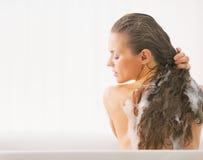 Młoda kobieta płuczkowy włosy w wannie Fotografia Royalty Free