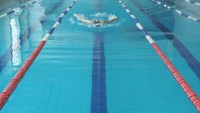 Młoda kobieta pływa motyliego uderzenia styl w błękitne wody salowym biegowym basenie w gogle i nakrętka zbiory wideo