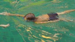 Młoda kobieta pływacki instruktor uczy berbeć chłopiec dlaczego pływać w basenie zbiory