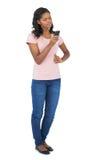 Młoda kobieta patrzeje jej telefon komórkowego z ręką na biodrze Obraz Stock