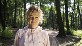 Młoda kobieta patrzeje kamerę i ono uśmiecha się w parku w różowej bluzie sportowa zbiory wideo