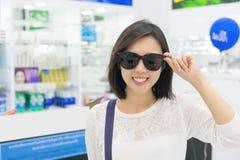 Młoda kobieta patrzeje kamerę w sklepie w okularach przeciwsłonecznych Zdjęcia Stock