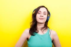 Młoda kobieta patrzeje kamera podczas gdy słuchający muzykę w błękicie Obraz Royalty Free