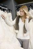 Młoda kobieta patrzeje metkę bridal toga w butiku Fotografia Royalty Free