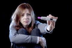 Młoda kobieta patrzeje nieszczęśliwa okaleczał trzymać ciążowego testa pozytywnego wynika i szokował Zdjęcia Stock