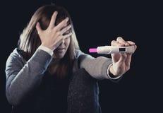 Młoda kobieta patrzeje nieszczęśliwa okaleczał trzymać ciążowego testa pozytywnego wynika i szokował Zdjęcia Royalty Free