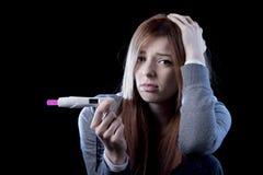 Młoda kobieta patrzeje nieszczęśliwa okaleczał trzymać ciążowego testa pozytywnego wynika i szokował Obrazy Stock