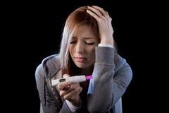 Młoda kobieta patrzeje nieszczęśliwa okaleczał trzymać ciążowego testa pozytywnego wynika i szokował Obraz Stock