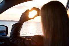 Młoda kobieta patrzeje out samochodowego okno przy zmierzchem na morzu Serce robić z rękami obraz stock