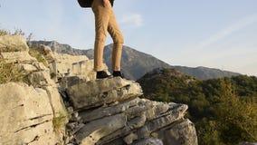 Młoda kobieta patrzeje pięknego góra szczyt z plecakiem na krawędzi halnej falezy zbiory wideo