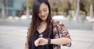 Młoda kobieta patrzeje at the time z uśmiechem zdjęcia royalty free