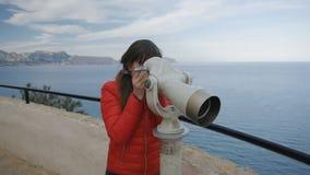 Młoda kobieta patrzeje w teleskop od obserwacja pokładu na dennym tle w czerwonej bąbel kurtce zbiory wideo