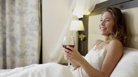 Młoda kobieta pije czerwone wino na łóżku zbiory