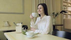 Młoda kobieta pije herbaty w kawiarni zdjęcie wideo