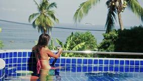 Młoda kobieta pije kawę na krawędzi nieskończoność basen w bikini, widok na ocean 3840x2160 zbiory wideo