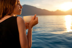 Młoda kobieta pije kawę na molu przy wschodem słońca fotografia stock