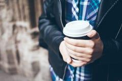 Młoda kobieta pije kawę na ulicie podczas gdy chodzący w centrum miasta Obraz Stock
