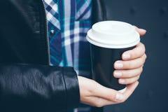 Młoda kobieta pije kawę na ulicie podczas gdy chodzący w centrum miasta Zdjęcia Stock