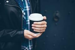 Młoda kobieta pije kawę na ulicie podczas gdy chodzący w centrum miasta Fotografia Royalty Free