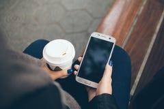 Młoda kobieta pije kawę na ulicie podczas gdy siedzący na ławce na zimnym zima dniu Zdjęcia Royalty Free