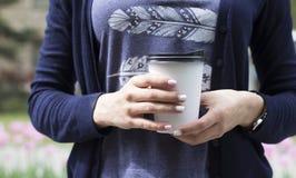 Młoda kobieta pije kawę od rozporządzalnej filiżanki Fotografia Royalty Free