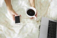 Młoda kobieta pije kawę w jej łóżku w domu Obraz Stock