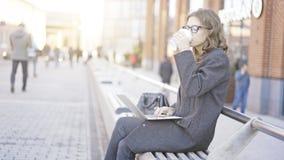 Młoda kobieta pije kawę z laptopem, ulica Zdjęcie Royalty Free