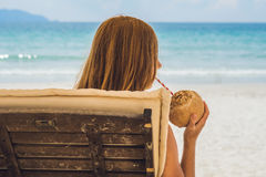 Młoda kobieta pije kokosowego mleko na bryczce na plaży Fotografia Royalty Free