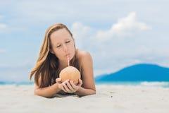 Młoda kobieta pije kokosowego mleko na plaży Zdjęcie Royalty Free