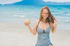 Młoda kobieta pije kokosowego mleko na plaży Fotografia Stock