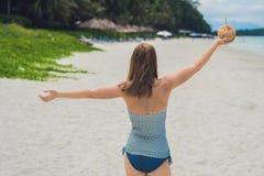 Młoda kobieta pije kokosowego mleko na plaży Zdjęcia Royalty Free