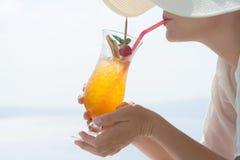 Młoda kobieta pije koktajl cieszy się wspaniałego widok Santorini blisko basenu obrazy stock
