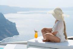 Młoda kobieta pije koktajl cieszy się wspaniałego widok Santorini blisko basenu zdjęcie royalty free