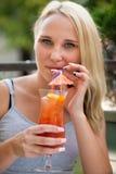 Młoda kobieta pije koktajl plenerowego na gorącym lata popołudniu wewnątrz Fotografia Royalty Free