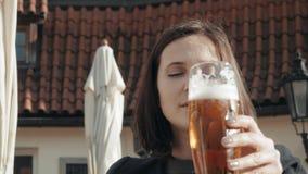 Młoda Kobieta Pije szkło piwo W Ulicznej restauraci Dziewczyna Cieszy się piwo W kawiarni Na ulicie Na słonecznym dniu zbiory wideo
