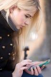 Młoda kobieta pisać na maszynie na telefonie Obrazy Stock