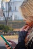 Młoda kobieta pisać na maszynie na telefonie Fotografia Royalty Free