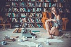 Młoda kobieta pisarz w biblioteki zajęcia kreatywnie śmiać się w domu obraz royalty free