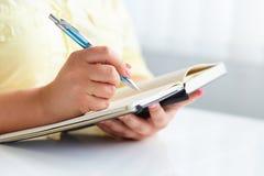 Młoda kobieta pisze czarny dzienniczek obraz stock