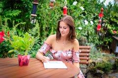 Młoda kobieta pisze w lato ogródzie w dzienniczku lub notatniku zdjęcia stock