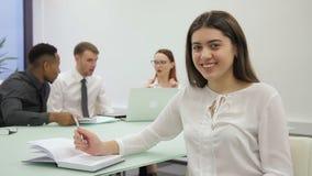 Młoda kobieta pisze wtedy patrzeć naprzód w nowożytnym biurze, siedzący zdjęcie wideo