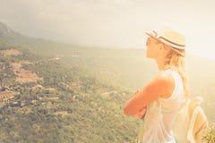 Młoda kobieta pobyt przy krawędzią patrzeje nad ekspansywnym widokiem równiny i góry faleza zdjęcie stock