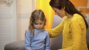 Młoda kobieta pociesza małej córki, wzruszające dziewczyny stawia czoło tenderly, bliskość zbiory