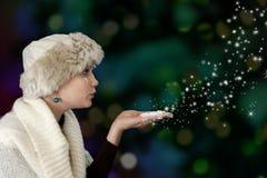 Młoda kobieta podmuchowy śnieg Obraz Stock