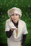 Młoda kobieta podmuchowy śnieg, zielony tło Zdjęcia Stock