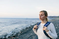 Młoda kobieta podróżnik w biel ubraniowej pozyci na brzeg i spojrzeniach przy morzem Fotografia Royalty Free
