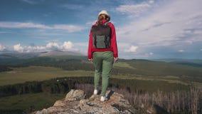 Młoda kobieta podróżnik z plecaka i kapeluszu stojakami na krawędzi falezy w górach i podziwia widok zdjęcie wideo
