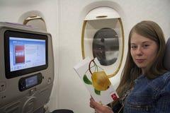Młoda kobieta podróżnika menu czytelnicza samolotowa karta Zdjęcia Royalty Free