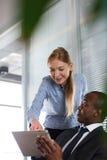 Młoda kobieta pokazuje coś na cyfrowej pastylce męski kolega w biurze Fotografia Stock